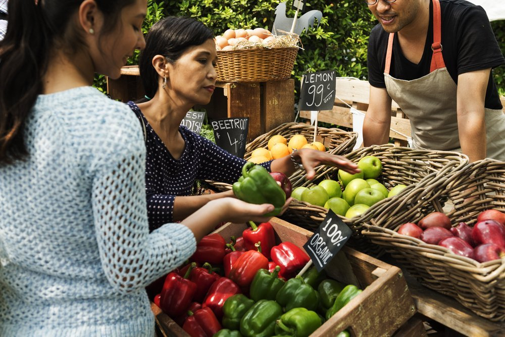 People buying fresh vegetables and fruits from a local market