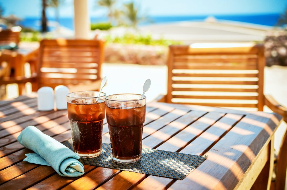Two glasses of cold cola on sunny day at the beach