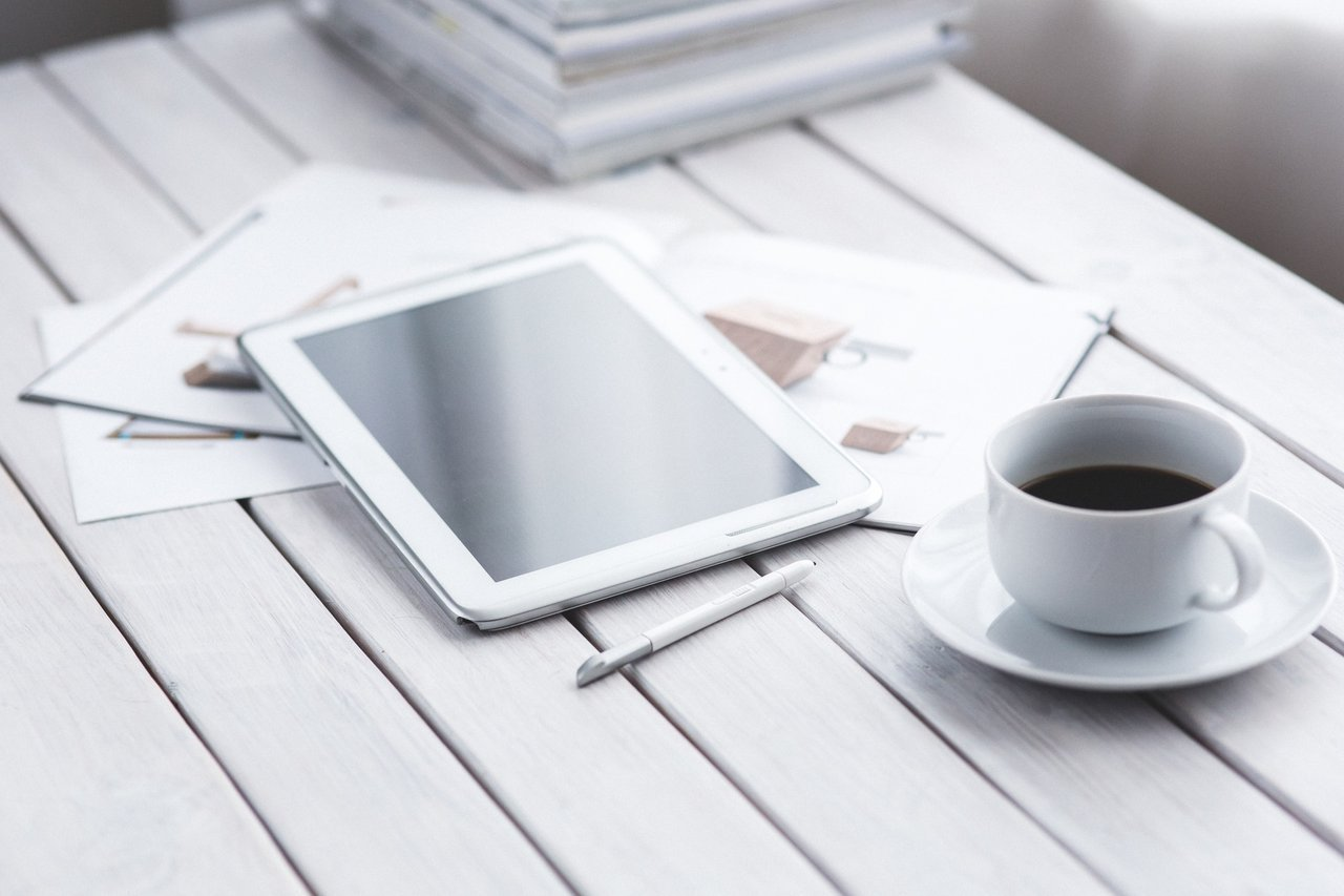 tablet, papers and coffee on desk