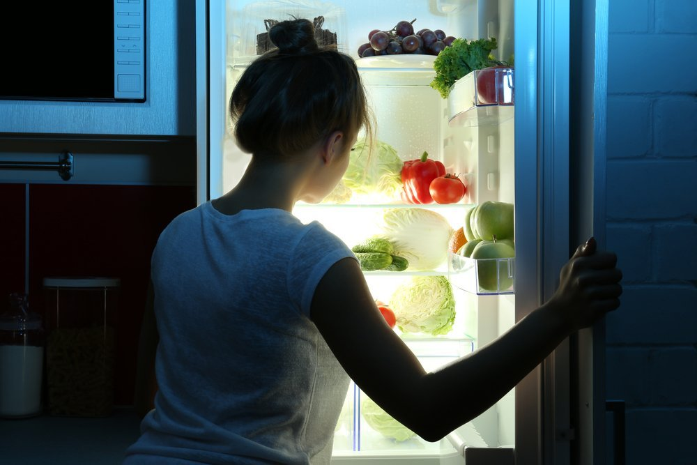 Woman looking through a fridge at night