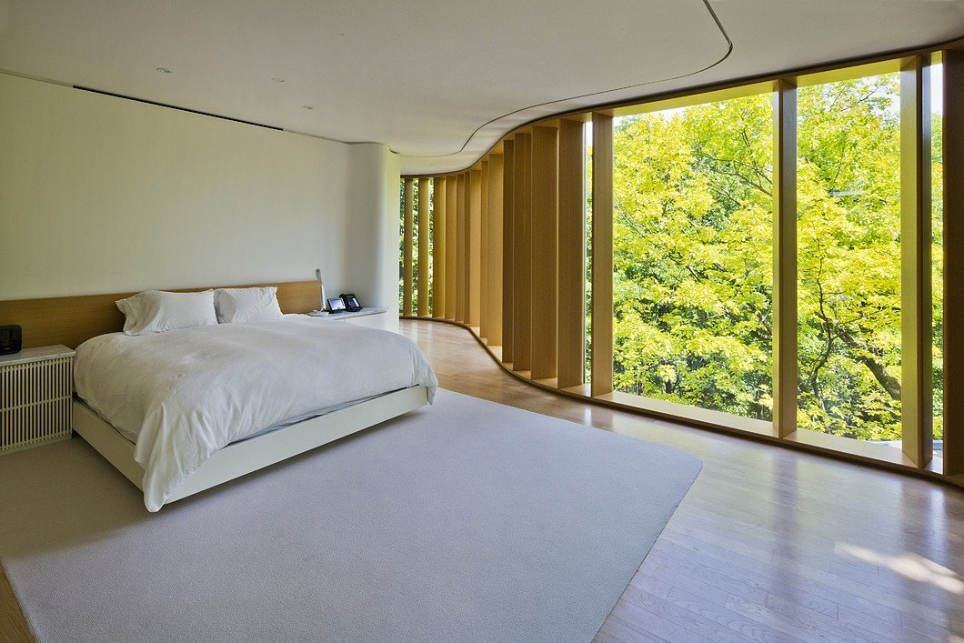 Floor to ceiling curved windows in bedroom