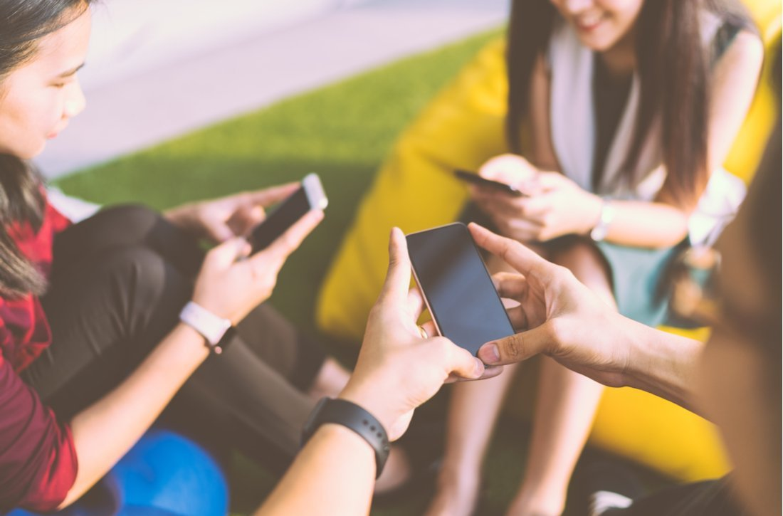 Group of friends using mobile phones
