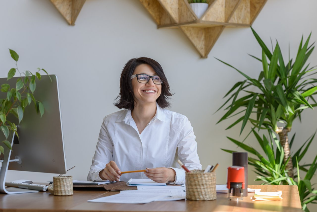 Woman Smiling Sitting at Desk with Plants