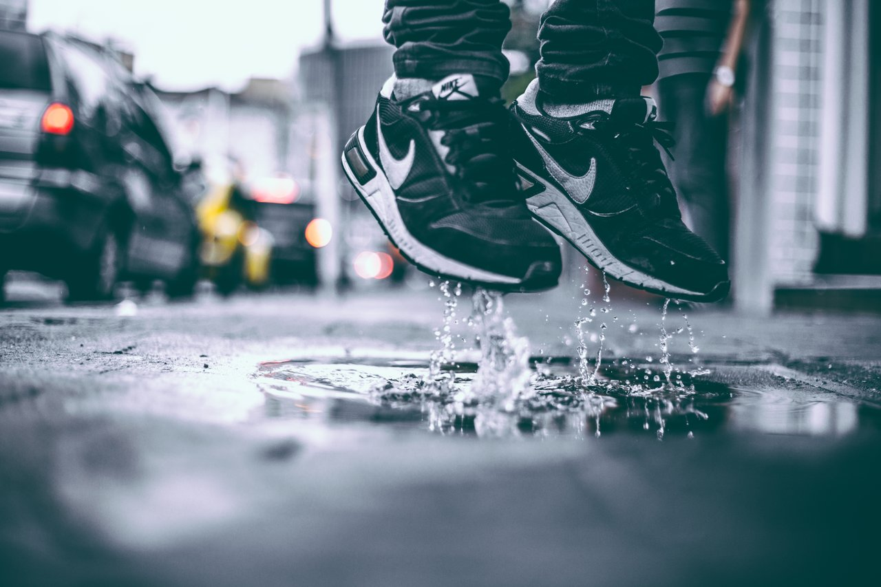 black leather sneakers in rain puddle