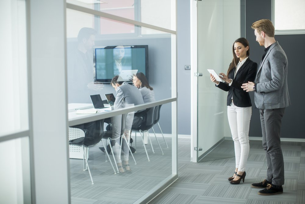 Young professionals using technology to book a room in office