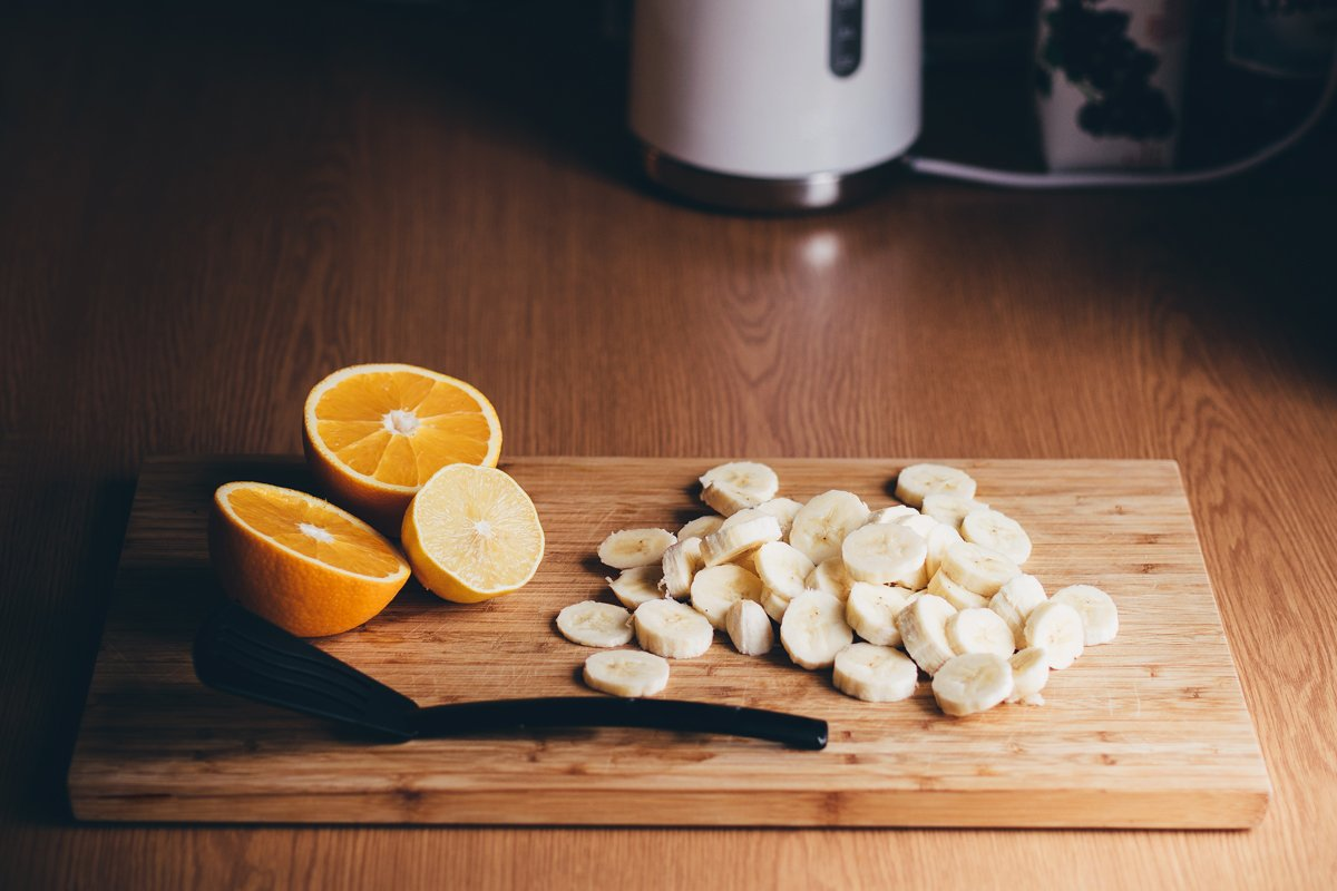 chopped bananas and oranges on cutting board