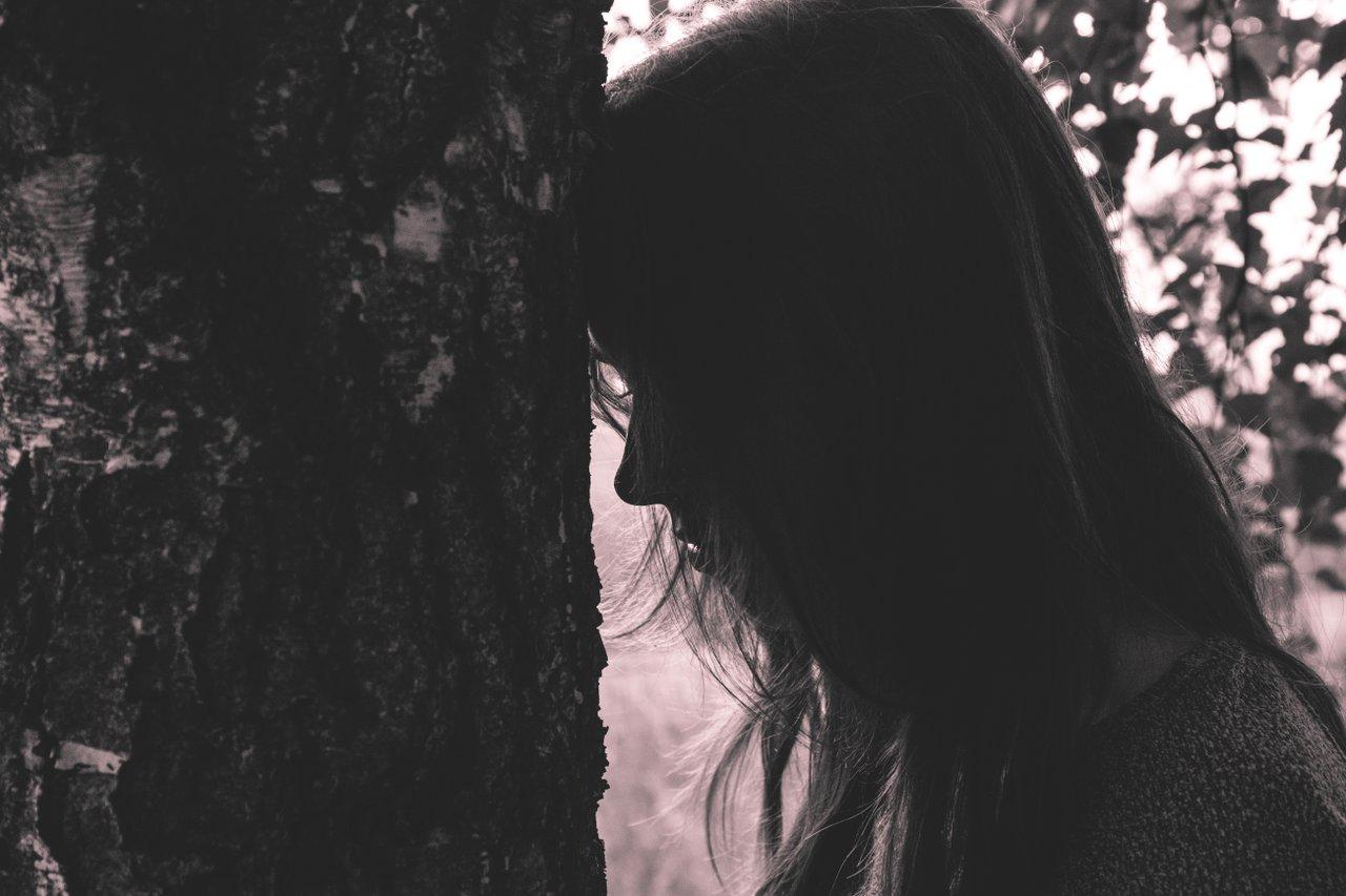 sad teen facing a tree