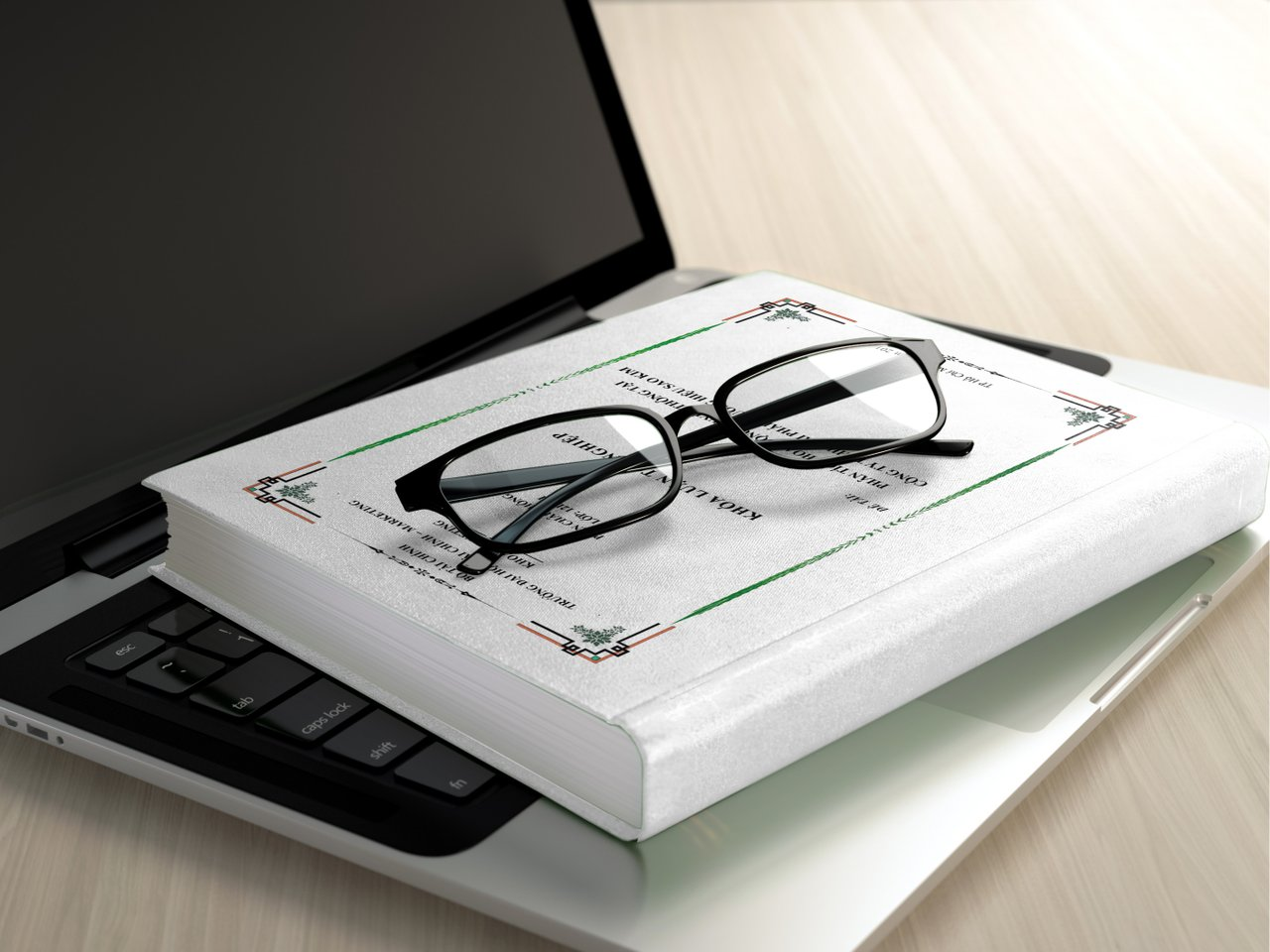 glasses, book and laptop on table