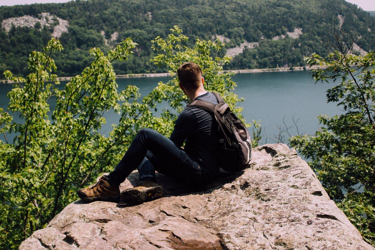 calm teen sitting on rock