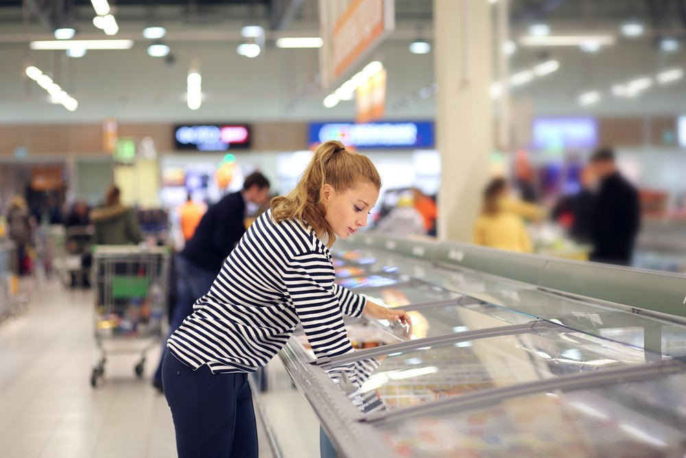 Woman shopping for frozen fish at grocery store