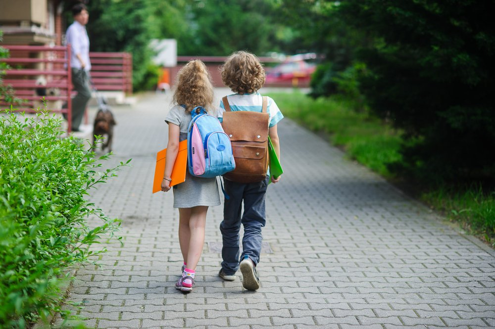 Two young children walking to school