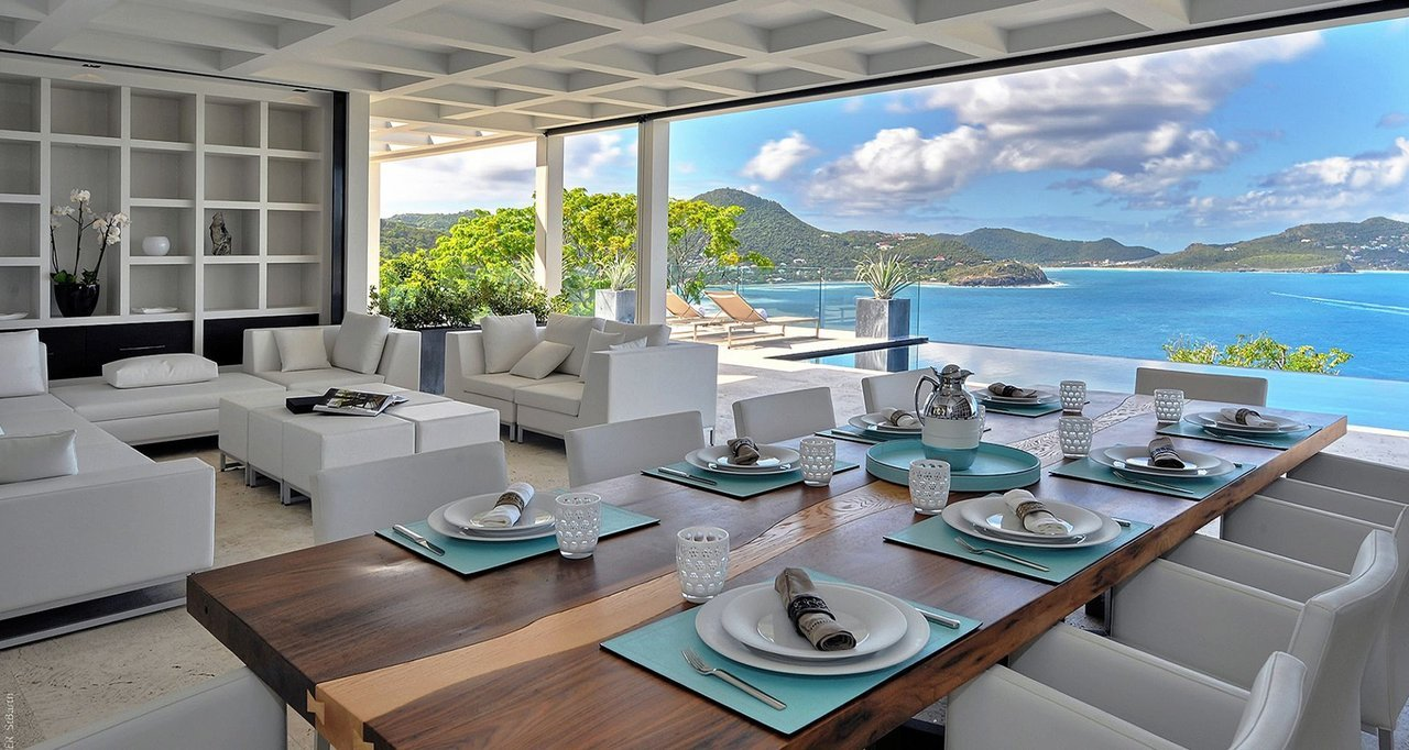 The luxurious, all-white living and dining room of La Petite Sereine in St. Bart's looks out onto the sea in the Caribbean.
