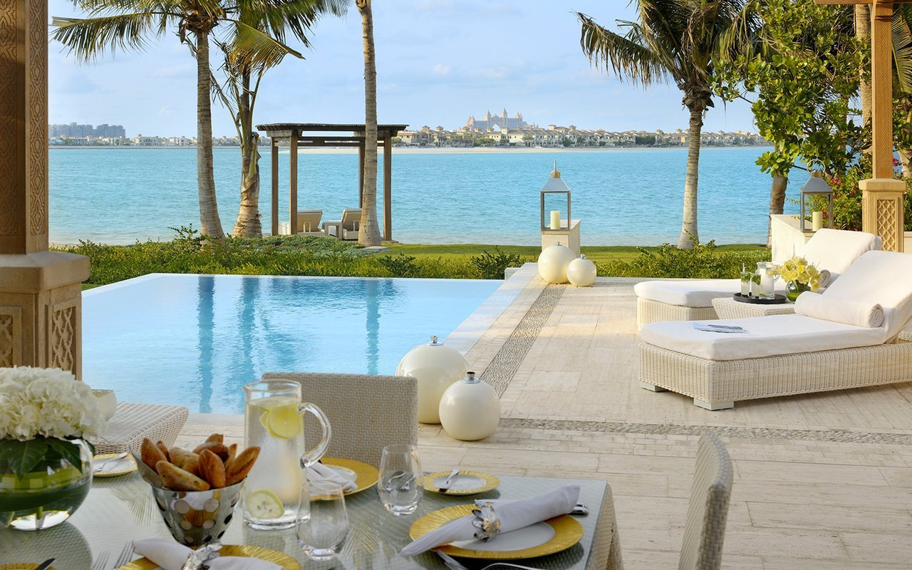 Pool of luxurious villa in Dubair overlooks palm trees, lake, and modern Dubai skyline.