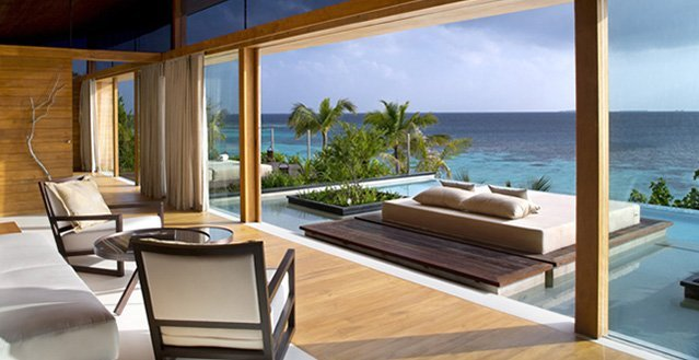 Large, oversized window of modern villa faces out onto Indian Ocean in Maldives.