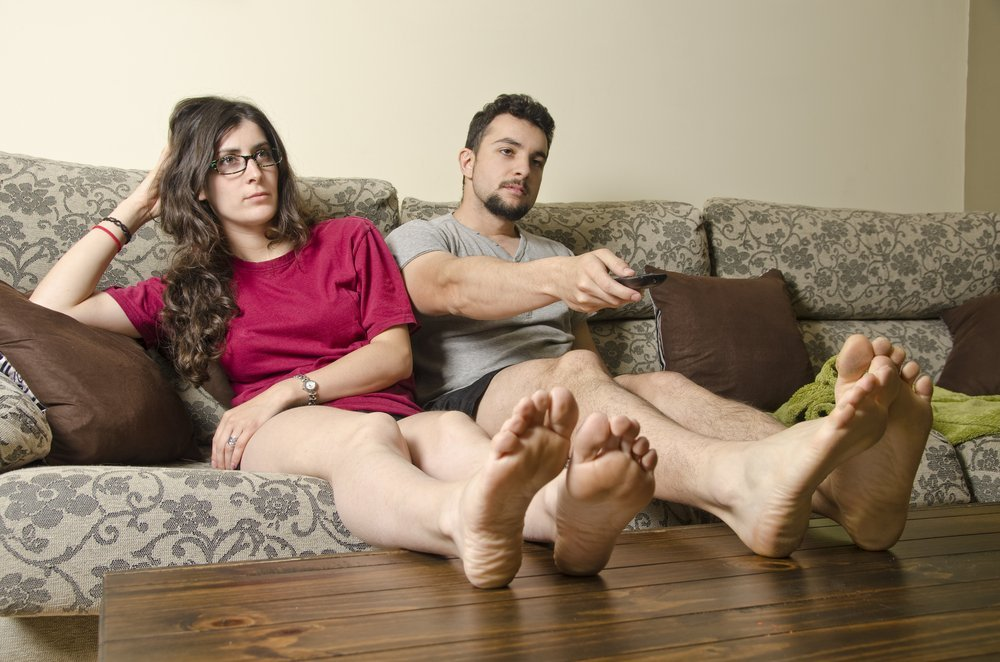 couple on couch staring at tv looking bored