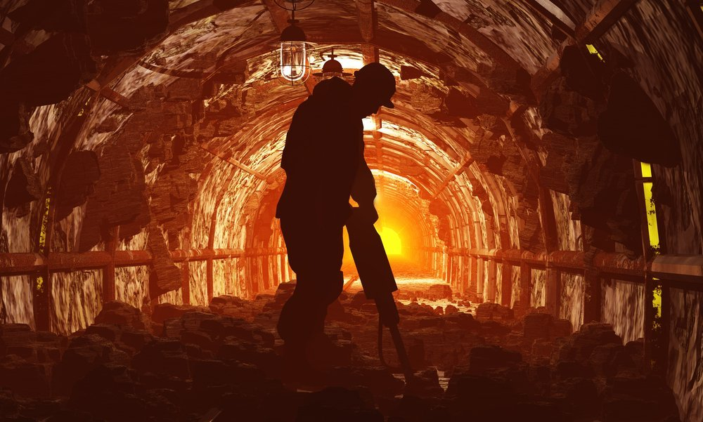 Silhouettes of worker in a mine.