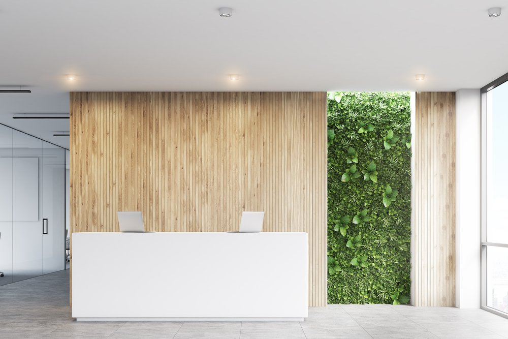 Bright reception area in office space with a plant wall