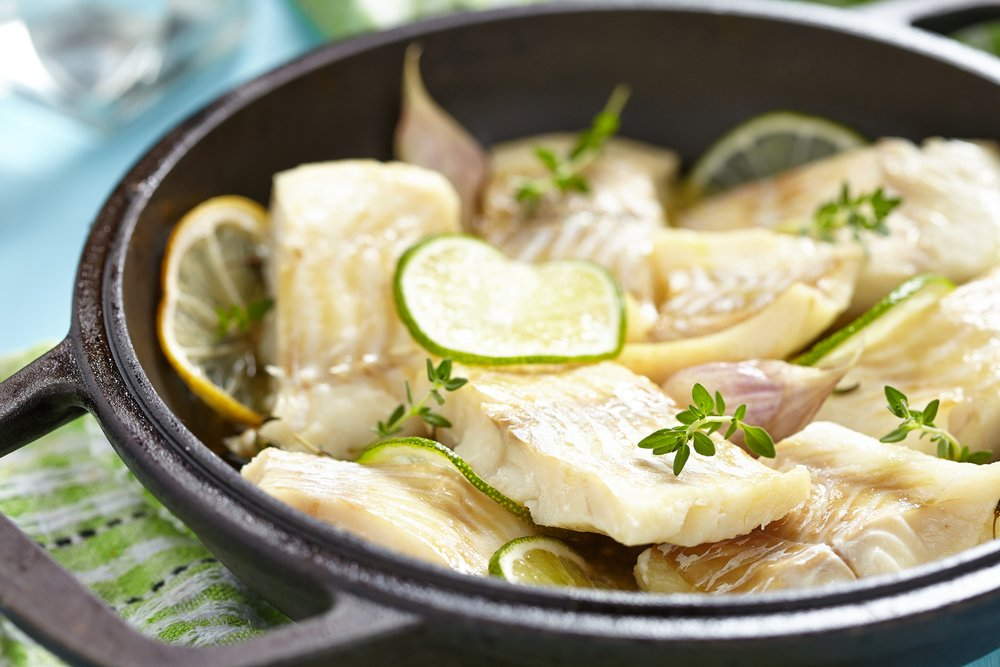 Baked fish fillet with lemon, lime, garlic and themy