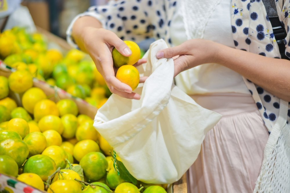 Woman using cotton bag at local food market