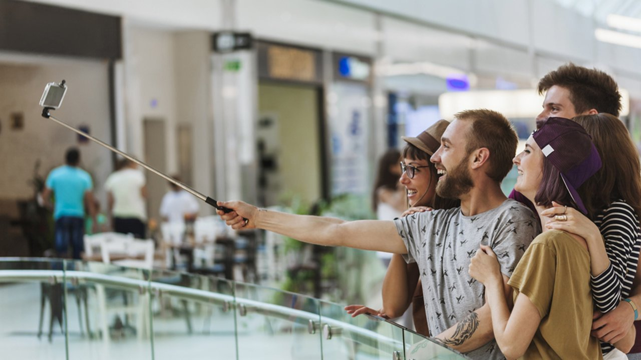 Friends taking selfie with a smartphone inside the mall