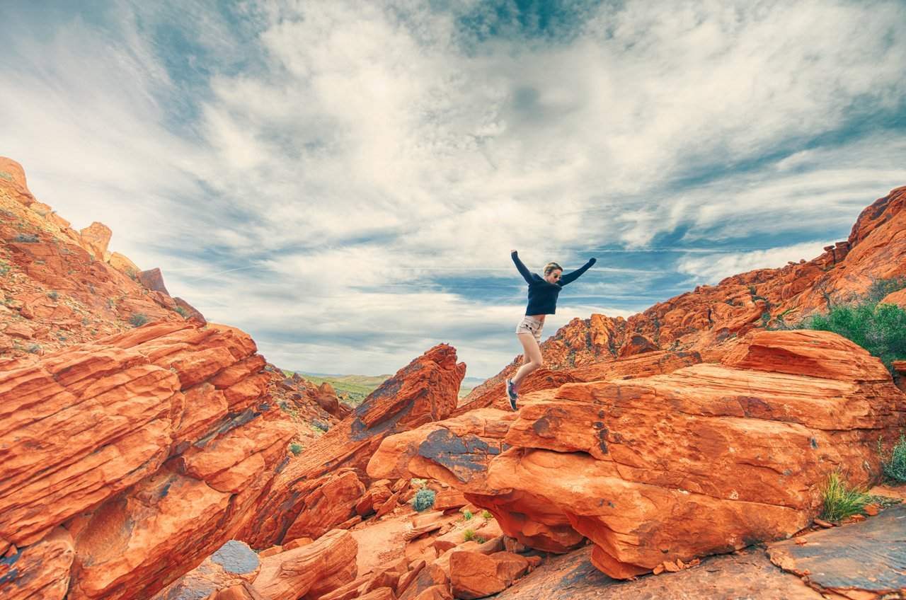 Teen jumping and running in picturesque national park