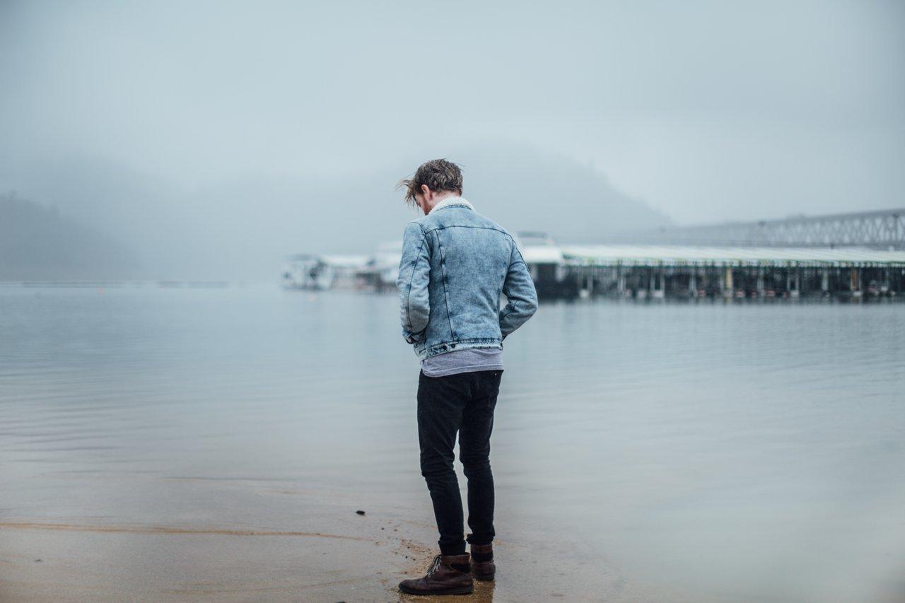 Teen boy standing at water's edge