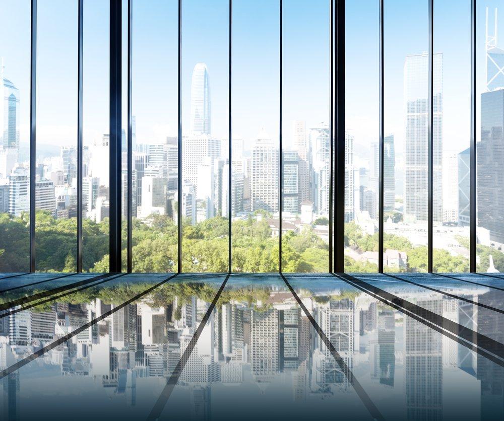Green city viewed through modern windows