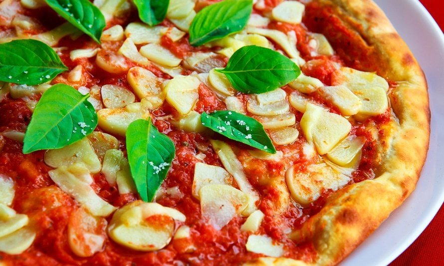Closeup of pizza with fresh basil Foods Impact the Environment
