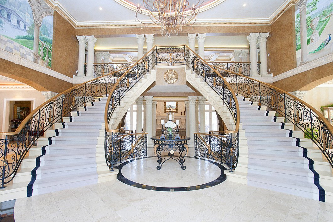 Twin marble staircases and chandelier in a luxury home