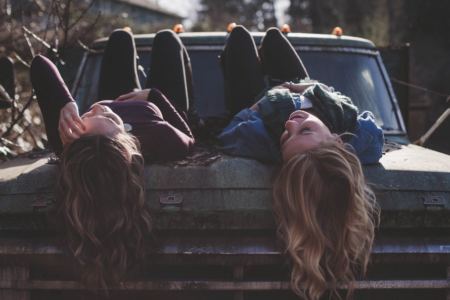 Two friends on the hood of a car