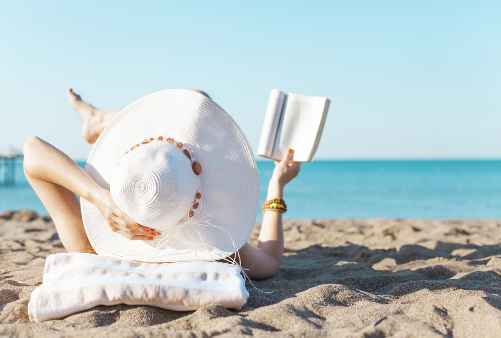 Woman in Hat Reading on Beach