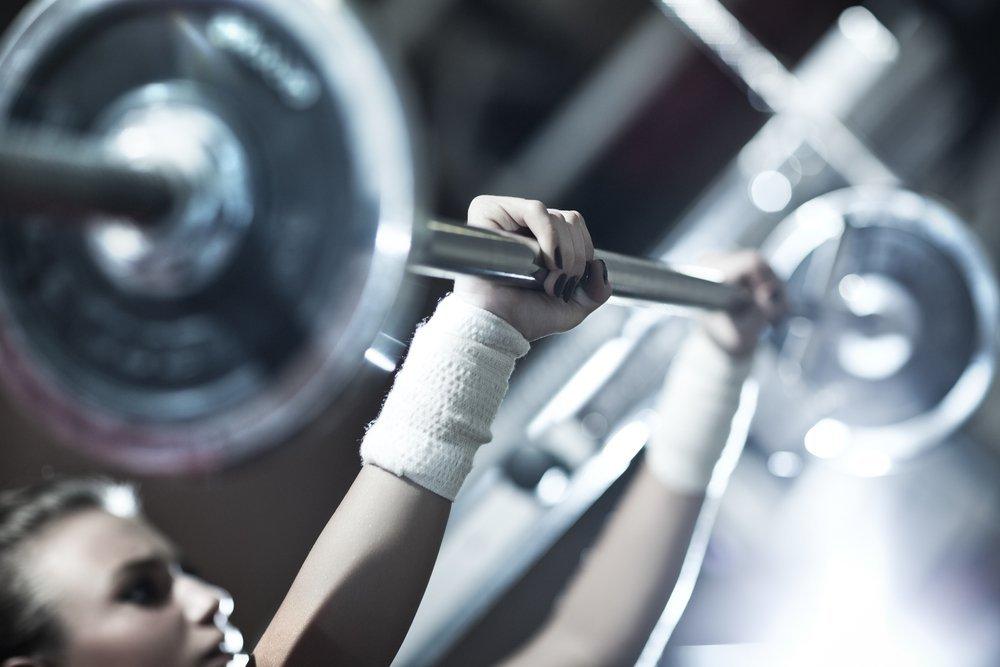 woman lifting weights bar