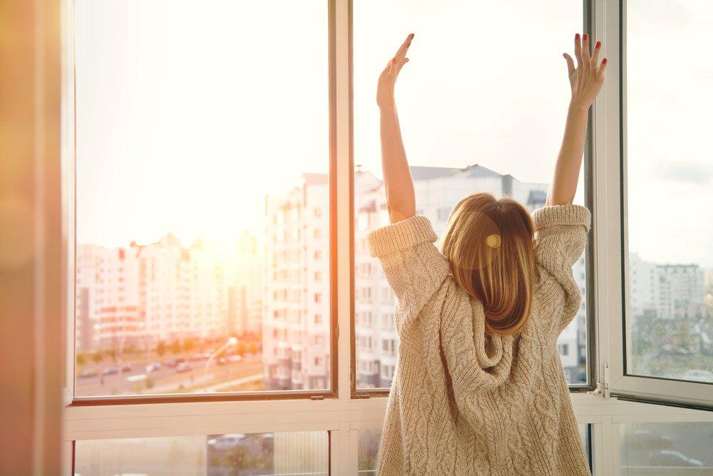Happy woman by window